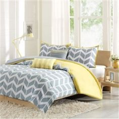 Twin/Twin XL 4-Piece Chevron Stripes Comforter Set in Gray White Yellow. This Twin/Twin XL 4-Piece Chevron Stripes Comforter Set in Gray White Yellow makes any bedroom fun and inviting. A gray and white chevron print runs along the comforter broken up by white vertical stripes. The reverse side is yellow adding charm and color to this comforter set. The same yellow borders the matching chevron print on the two shams. Includes the matching yellow and gray decorative pillows.  Twin/Twin XL…