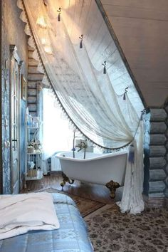 Romantic bath nook. Clever use of hooks for the curtain on the sloped ceiling.