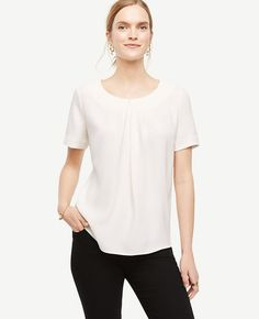 """Detailed with asymmetric front pleats and a soft matte jersey back, our flowy mixed media top is perfect to wear - any day of the week. Jewel neck. Short sleeves. Hidden back zipper with hook-and-eye closure. 24 1/2"""" front length; 23 3/4"""" back length."""