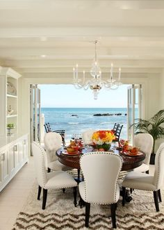 Beachside dining room with fabulous clear glass chandelier and a gorgeous view of the ocean. Love the glossy white beams. Not a fan of the rug.
