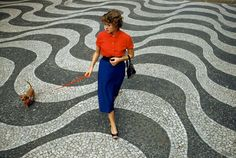 A woman walks a dachshund across pavement with undulating wave patterns in Rio de Janeiro, Brazil, March 1955. (Photograph by Charles Allmon...