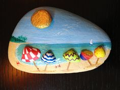 Rock painting... look closely, the umbrellas are small shells that have been painted and glued to the rock!