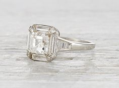 Vintage Art Deco platinum engagement ring centered with a GIA certified 1.26 carat asscher cut diamond with G color and VS1 clarity. Accented with baguette cut diamonds. Circa 1925