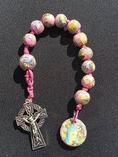 Van Gogh single decade rosary. Wood beads hand decorated with tissue paper and art book pages- collages from print of Van Gogh's Irises. Medal is a wood disc hand decorated with repurposed prayer cards. Beads strung on colorful hemp cord.
