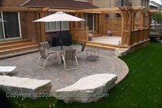 Like the paver patio with the big seating rocks; just replace that table with a fire pit.