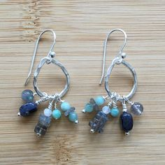 """Hammered Karen Hill Tribe silver, pear shaped links swing above gemstones wire-wrapped by hand. The mix of genuine labradorite, natural emerald, rainbow moonstone, and dumortierite are versatile and stunning. The earrings drop 1.75"""" from the top of sterling silver ear wires."""