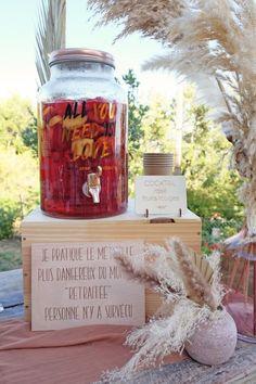 """Cette fontaine à boissons en verre transparent a une contenance de 4 litres environ, elle est décorée d'une belle phrase de couleur rose gold. Mariage, anniversaire, EVJF ou baptême, placez cette bonbonne à jus ou à limonade sur une jolie table décorée pour rafraîchir vos convives. Elle dispose d'un robinet en plastique rose gold et d'un couvercle à visser en métal rose gold. Pensez a ajouter une pancarte """"Servez-vous"""" ou une jolie ardoise pour indiquer la saveur à vos invités. Fruit Rose, Cocktail Fruit, Candle Jars, Candles, Saveur, Ajouter, Transparent, Table, Rose Drink"""