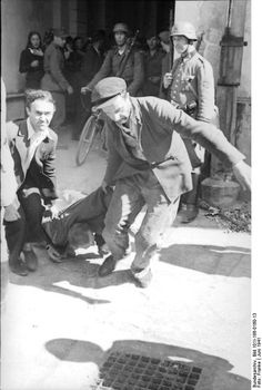 Russia, June 1941: Men in civilian clothes grab a Jewish man who has beaten down outside a building guarded by Germans; unidentified location. Note the woman on the left background gasping at the sight of the violence dealt upon the victim. The Germans are of course disinterested.