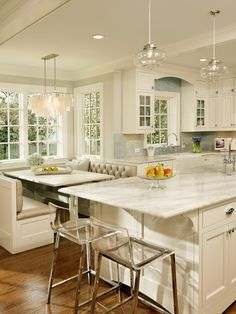 Love the white, marble countertops, island and a breakfast nook. beautiful