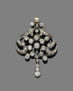 A late 19th century diamond brooch/pendant necklace The openwork cartouche of scrolling design, set throughout with cushion-shaped, old brilliant and rose-cut diamonds, mounted in silver and gold