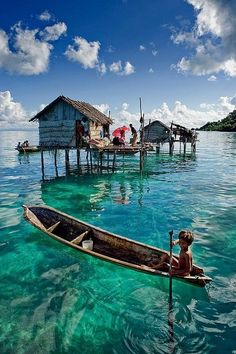 Blue skies. Clear water. Houses on stilts in the water. Canoes. Indonesia.
