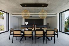 In this modern house, the matte black Bulthaup kitchen has been paired with a dark countertop, and shares the space with the dining room. Artistic gold pendant lights anchor the large dining table and chairs in the room.