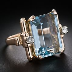 Retro Aquamarin and Diamond ring. A serene and soothing pastel blue aquamarine, weighing approximately 12.75 carats, is artfully presented between a pair of sparkling round diamonds set atop modernly stylized scroll mot