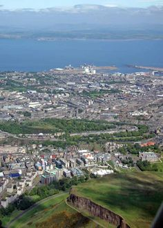 Edinburgh and Leith - view to the north from a helicopter  FOREGROUND, LEFT: Dumbiedykes housing  FOREGROUND, CENTRE:  Salisbury Crags in Queen's Park  MID-DISTANCE, LEFT: Calton Hill and former Royal High School  MID-DISTANCE, CENTRE: Dynamic Earth (white roof)  Scottish Parliament (behind dynamic earth)  MID-DISTANCE, RIGHT: Holyrood Palace  BACKGROUND: Leith Western Harbour (with new apartments)  Firth of Forth  Fife and beyond