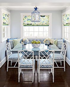 White bamboo dining chairs accented with blue chevron seat cushions sit in a pretty blue breakfast nook at a glass and chrome x-base dining table lit by a blue pagoda lantern.