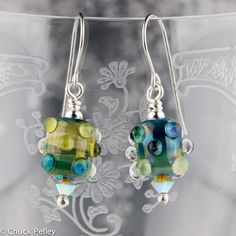 "Handmade lampwork glass bead earrings in green, gold, blue iridescent silver laden glass with Swarovski crystal tips. Surgical steel ear wires. Approximately 33 mm (1.3"") from top of ear wire to tip of earring."