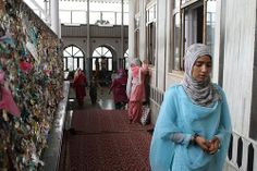 A woman walks past the corridor at the Makhdoom Sahib shrine after tying a wish thread on the carved wall in Srinagar, India