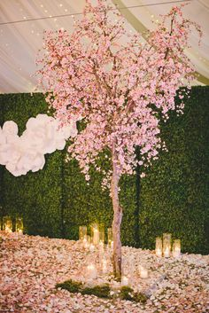 The cherry blossom trees had the floors entirely covered in its pink petals, decorating the area around the sweetheart table. Candles in glass cylinder vases that ranged in height added a romantic ambience, also scattered on the ground. Blossom Tree Wedding, Cherry Blossom Party, Blossom Trees, Cherry Blossom Centerpiece, Cherry Blossom Decor, Cherry Blossoms, Wedding Centerpieces, Wedding Decorations, Japanese Wedding
