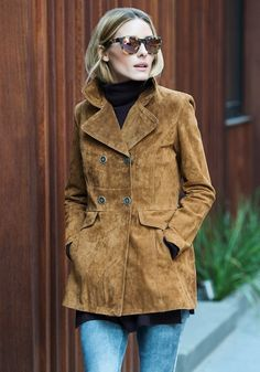 Olivia Palermo wears a suede jacket, turtleneck, jeans, and mirrored sunglasses