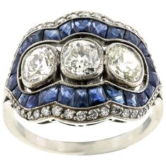 "Art Deco Sapphire Diamond Platinum Ring. A beautiful example of an Edwardian -- often called Art Deco in this ring style -- three diamond ring, these half-carat old European-cut diamonds set in platinum and surrounded with calibré-cut sapphires and full-cut diamonds, in a curved platinum mounting with beaded edging. The diamonds total weight is approx. 1.50 carats and the center diamond, I2. The ring measures 3/4"" x 1/2"" and curves around the finger. c 1920"