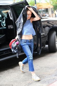 Caught in the downpour: Earlier on in the week, the actress wasn't as lucky with her wardrobe choice, as she was forced to shelter under her jacket in a rain-drenched New York