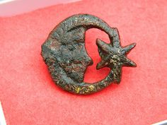 A cast Medieval bronze retainer's badge or mount showing the 'sun, moon and star' emblem, See Mitchiner, M., Medieval Pilgrim and Secular Badges, page 195 for similar pewter examples. The 'star and crescent' (sun, moon and star) symbols were a traditional badge of the Plantagenets during the period Richard I to Edward I and were also popular in the 14th century. Measures 25mm X 23mm.