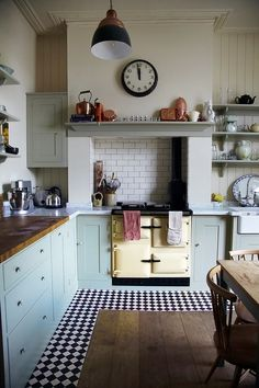 Pale cupboards with wooden countertop. Vintage light, bold clock, open shelving