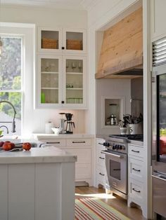 White inset shaker cabinets, rustic wood vent hood, marble counters