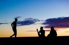 Silhouettes of a small group of people relaxing, one standing and two sitting, against a partly cloudy sunset