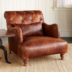"""ALCAZAR LEATHER ARMCHAIR--Practical palatial seating in diamond-tufted, naturally shaded leather promising beauty, character and comfort for decades to come. Crafted in USA, using FSC certified wood and sturdy webbing construction. 24"""" x 14"""" lumbar pillow included. 33""""W x 42""""D x 32""""H."""