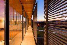 CASA SL. Quiebravistas de metal oxidado protegen el frente vidriado.