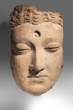 Visage de Bouddha, aux yeux mi-clos et au front orné de l'urna.  En terre cuite. (Restaurations).  H : 31 cm Art gréco-bouddhique du Gandhara (Ier - Ve siècle)