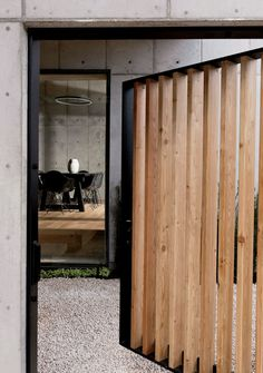 """Doors, Exterior, Wood, and Swing Door Type """"We talked about creating a sense of mystery when [guests] walked in from the street,"""" says Christopher. A gate swings open on a steel bar-stock frame to reveal a courtyard and the dining room beyond. Beton Design, Concrete Design, Timber Screens, Pivot Doors, Concrete Houses, Box Houses, Cedar Houses, Minimalist House Design, Types Of Doors"""