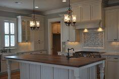 """The cabinets are """"antique white"""" and the walls color is Sherwin Williams Jogging Path SW 7638."""