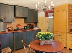 "This kitchen is in the home of Roger and Sylvia Libbey, in York County, Maine. The house was built ca. 1770 and has been in Roger's family since 1849. An antique New England table and chairs make it an ""eat in"" kitchen. A cooktop hides under the breadboard on the countertop; the oven is behind cupboard doors. The refrigerator is behind the tall mustard-colored cupboard."