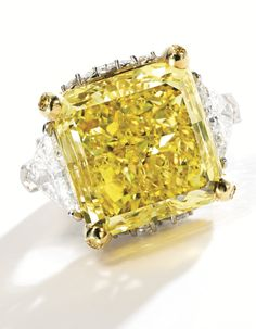 MAGNIFICENT PLATINUM, 18 KARAT GOLD, FANCY VIVID YELLOW DIAMOND, COLORED DIAMOND AND DIAMOND RING Centering a cut-cornered square modified b...
