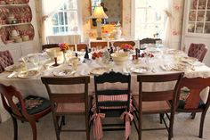 I like mismatched. Everything. Chairs, dishes, formal and whimsical at the same time. This is the table in the dining room, set for Thanksgiving. www.susanbranch.com