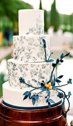 Understates elegance is the term for this cake with its teal floral toile pattern and sugar flowers.