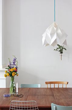 A beautiful picture of the white Moth XL lamp hanging over a table with some colorful flowers. Picture by Sara van de Borg. @saroetje
