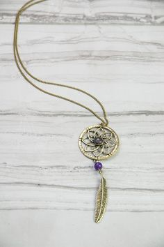 This antiqued gold chain necklace has a dream catcher pendant with a purple bead and gold feather charm is perfect for those bohemian dreamers. Chain measures 32''-35'' and charm drops 4'' long.