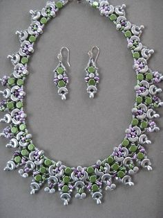This is a handcrafted Silver Arcos and Light Green Honeycomb hand beaded necklace and earring set. It also has silver pellet beads and Swarovski crystals and lavender super duos. The result is a beautiful, soft but dramatic, necklace set. One of my favorites. The earrings match the