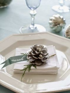 dress up a simple place setting with a pinecone and name tag cut from scrapbook paper and attached to a whitewashed pinecone studded with silver dragees