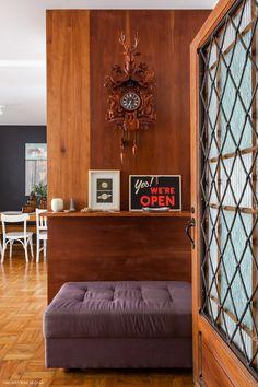 A entrada desse apê tem porta antiguinha e painel de madeira com relógio cuco.