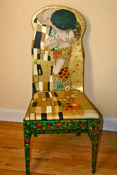 This upcycled painted chair pays tribute to Klimt's The Kiss painting. This piece of artwork is painted in acrylic blends and shades of gold,red, blue, yellow, tan and black and features an upholstered seat with duck cloth. The backside of the painted chair has also been done in Klimt's