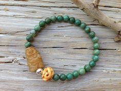 """EXTRAORDINARY LIFE BUDDHA BRACELET     """"The mind is everything. What you think you become.""""-Buddha  A carved hsiu jade Buddha is nestled in sterling silver, carved bone and african jade. Let it remind you to become something extraordinary. Stretch bracelet measures 7"""", sized to fit most wrists."""