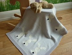This blanket is knit in stocking stitch with an all-round garter stitch border.The blanket is decorated with six rabbits which are worked in duplicate stitch (but you can knit them using the intarsia method if you like). There are charts showing the rabbit design and how to place them on the blanket.The tails of the rabbits are knitted separately as bobbles and then sewn onto the finished blanket.The sample was knit in BBB filati Martine (a DK yarn) with the rabbits worked in 4-ply and their…