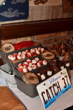 "Fishing ""reels"" and ""bobbers""  Bobbers are cake pops dipped in white chocolate melts, hardened and then dipped the other half in red melts. The reels are cookies dipped in chocolate. While they are still wet, put a big marshmallow in between two cookies."