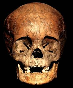 DAYAK TRIBE: HEAD HUNTING HUMAN TROPHY SKULL #15  HAND CARVED HUMAN SKULL WITH BOTTOM JAW.  THE DAYAK TRIBE, FROM BORNEO ISLAND  INDONESIA, CARVE DESIGNS INTO THE SKULLS  OF THEIR HEADHUNTED VICTIMS AND INSERT WOODEN FIGURES.