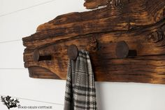 A piece of live-edge reclaimed wood looks even more rustic when you drive a few railroad spikes into it to serve as hooks.