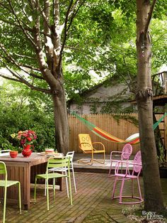 A great escape from the city, this cozy backyard is perfect for dinner parties. The homeowners painted a collection of chairs  bright colors to spread the festive atmosphere. They added a hammock for lazy reading sessions or an afternoon nap.
